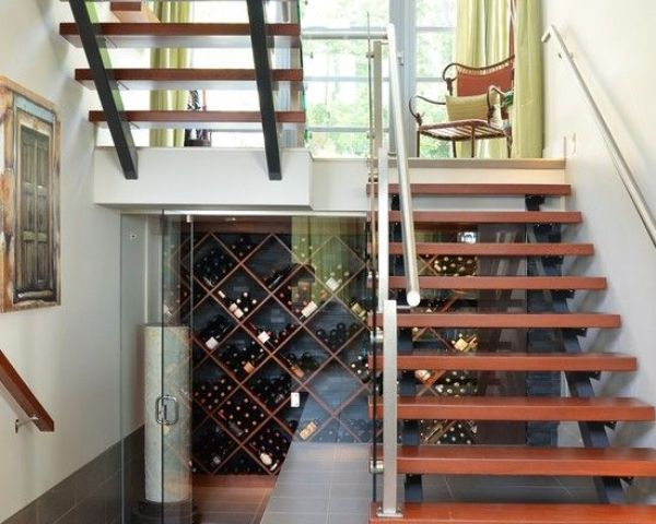 a stylish under the stairs wine cellar with glass doors and wooden shelves on the walls