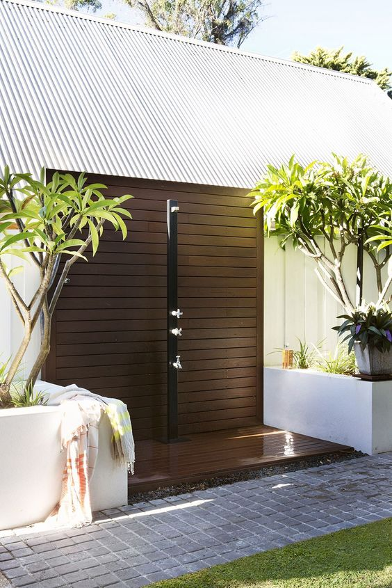 an outdoor contemporary shower with a dark stained wooden platform, potted trees around