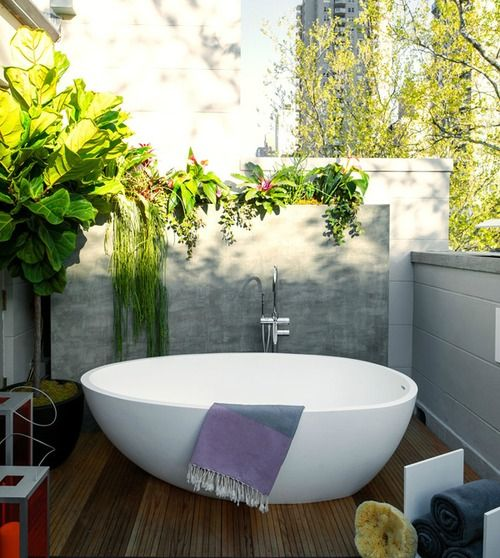 an outdoor deck with low walls all round to keep privacy yet have enough light, a stylish oval bathtub and lots of greenery