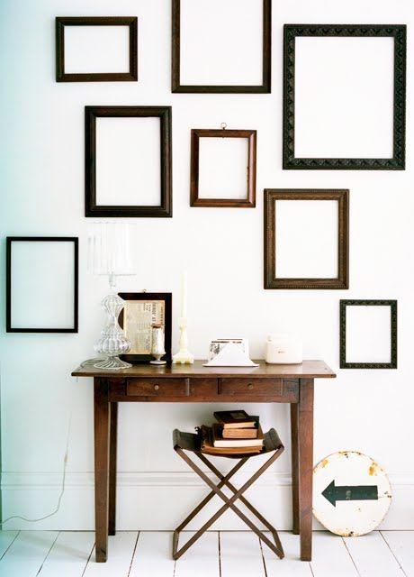 make a statement in a neutral space with dark empty frames and a dark stained desk