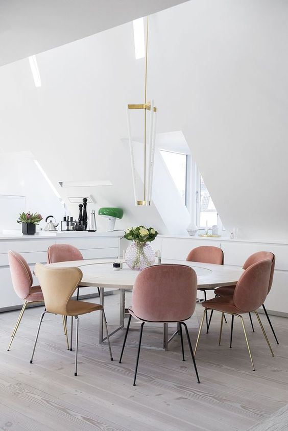 a contemporary dining space with dusty rose chairs for a colorful touch in the neutral space
