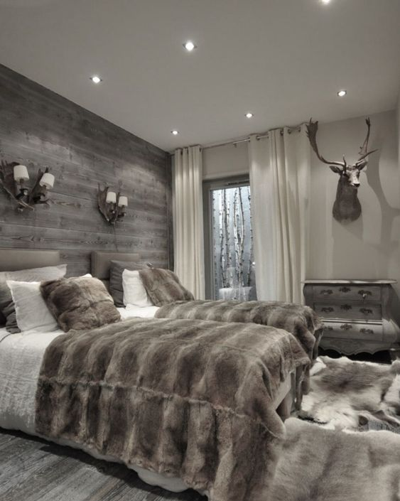 a double guest bedroom done in chalet style with a grey weathered wood wall for a statement