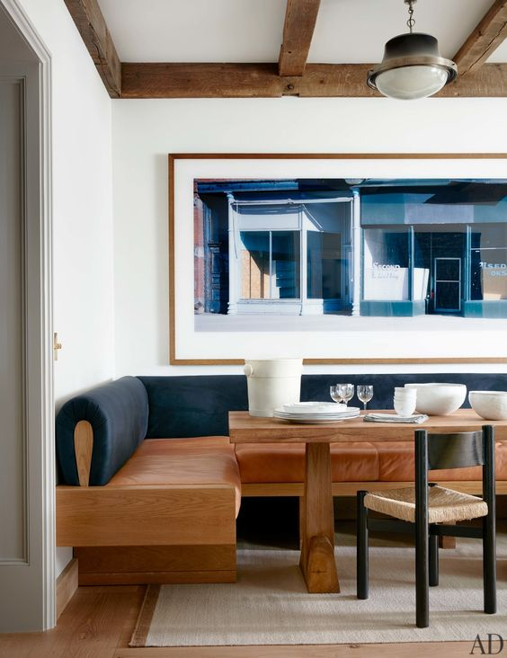 a modern dining space with a wood, leather and velvet banquette in contrasting colors