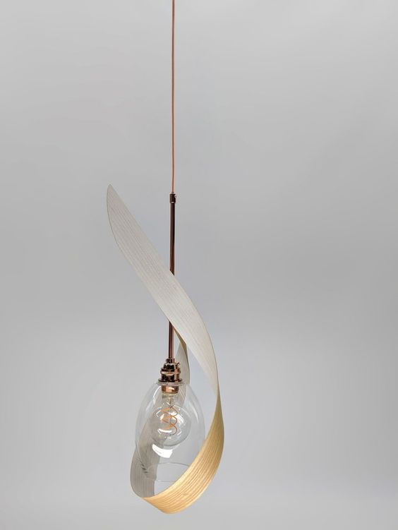 a sculptural pendant lamp made of bent plywood and a glass lampshade