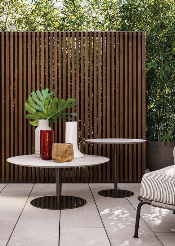 a tall stained wooden plank fance is ideal to hide your outdoor space from other people