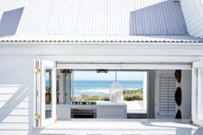 13 an all-white beach house with a folding window, a white bar counter and stools and the same window on another wall to see the views