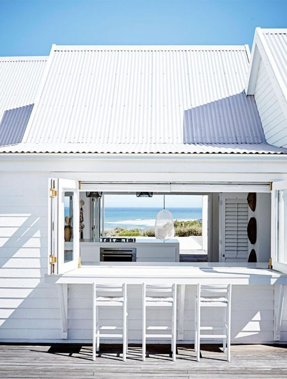 an all-white beach house with a folding window, a white bar counter and stools and the same window on another wall to see the views