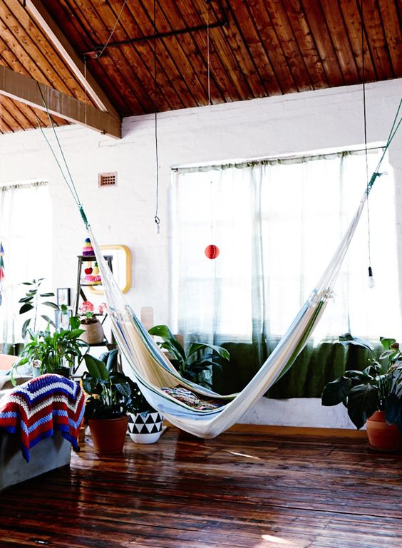 this indoor space feels like outdoors thanks to potted greenery, colorful textiles and a striped hammock