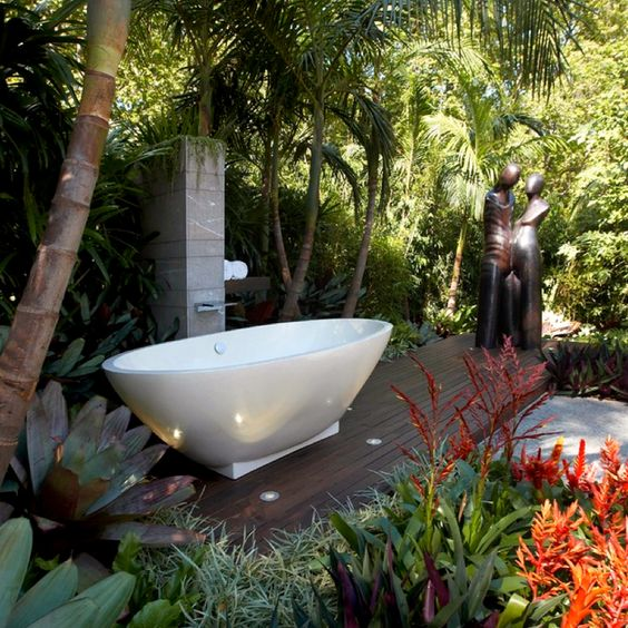 a backyard deck with some statues, a tile clad panel and an oval tub on a geometric base