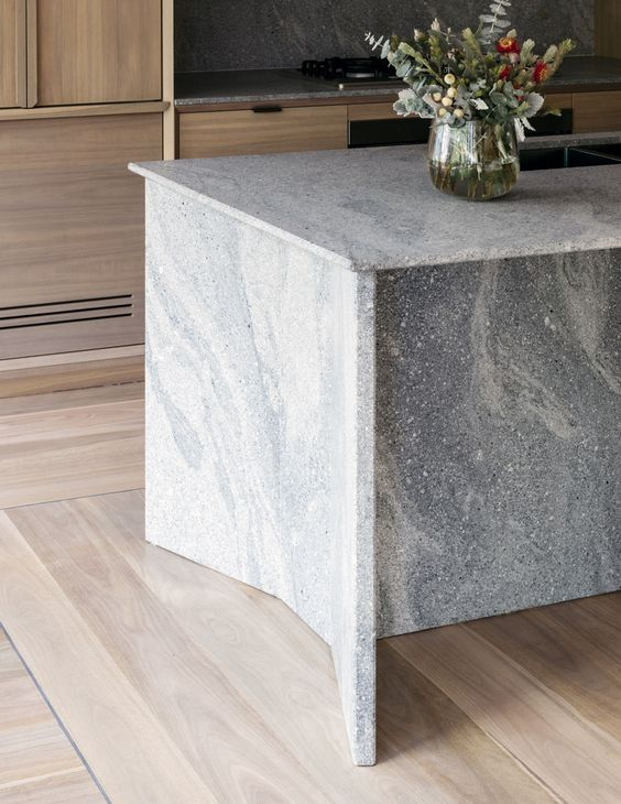a contemporary space of light colored wood and a grey granite kitchen island for a fresh feel