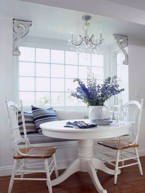 a nautical dining space with a built-in banquette seating and a round table