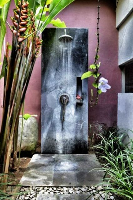 a tropical inspired outdoor shower with tropical plants and flowers and a concrete and plaster shower space