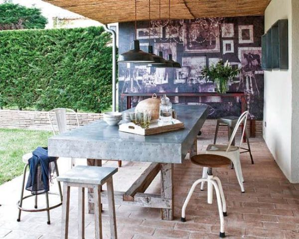 an industrial dining space with a metal covered table and all different chairs from industrial to rustic