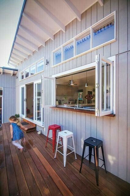 an outdoor bar with a bifold window to the kitchen is a cool space-saving idea