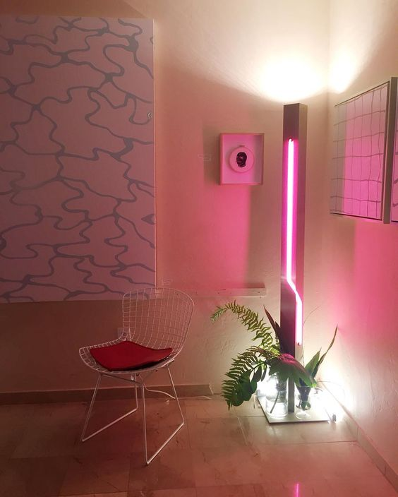 spruce up your space adding a party feel to it with a bright pink neon light and some tropical leaves