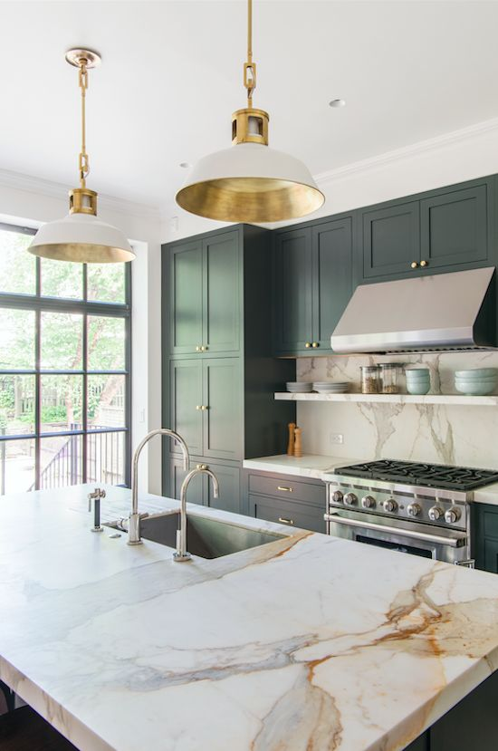 a chic art deco inspired kitchen with black cabinets, touches of gold and marble style granite countertops