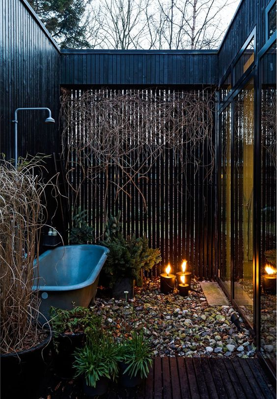 a contemporary space in a small private courtyard, with pebbles on the floor, candles and a grey bathtub