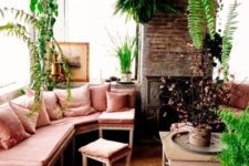 15 a neutral sunroom filled wiht a lot of potted greenery and with a corner bench in dusty rose
