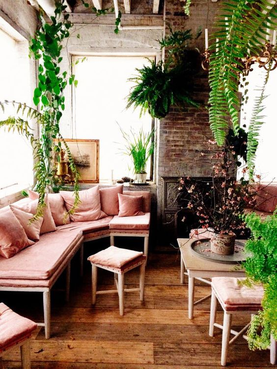a neutral sunroom filled wiht a lot of potted greenery and with a corner bench in dusty rose