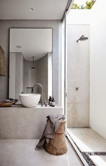 a small outdoor shower done with light colored concrete and pebbles is built up to the usual indoor bathroom