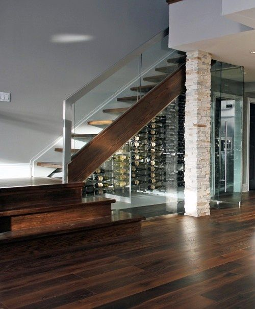 a whole wine room under the stairs with glass walls and lights inside looks very inviting