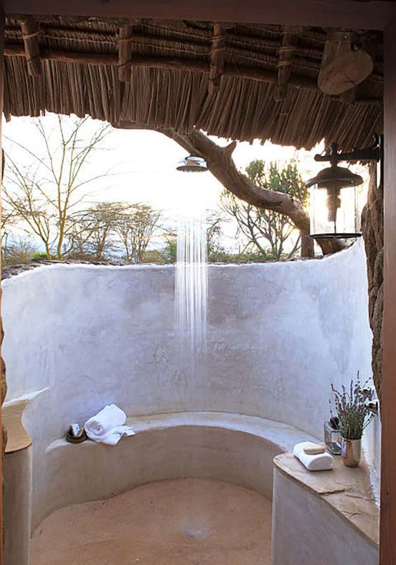 a comfy outdoor shower done with concrete and plaster, with a wooden roof over it and a rain shower on a branch