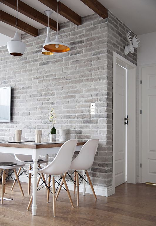 a light colored grey brick wall adds texture to the space and white furniture refreshes the area