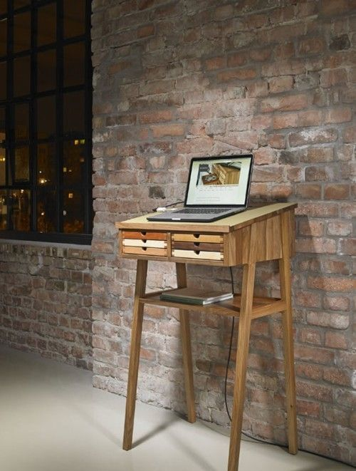 a small wooden standing desk with little colorful drawers is suitable for a laptop