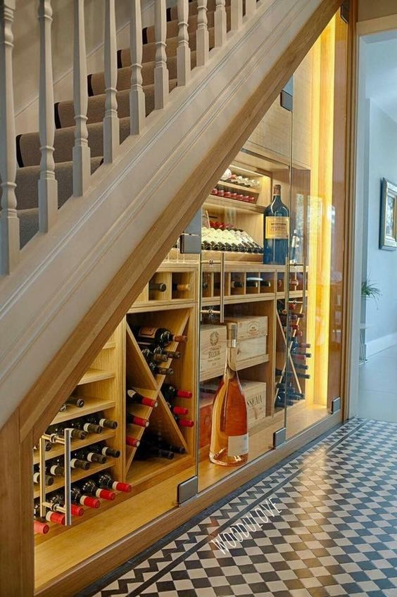 a wine cellar with glass doors and wooden storage units with additional lights to easily find a bottle