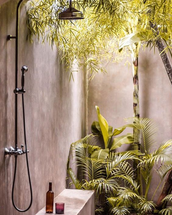 a concrete outdoor shower with hanging and planted greenery for a cool tropical feel