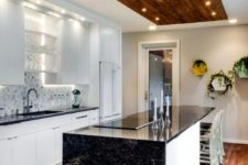 17 a contrasting black and white kitchen with black granite countertops and  touches of wood