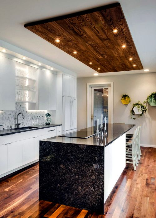 a contrasting black and white kitchen with black granite countertops and  touches of wood