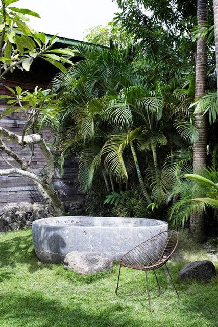 a gorgeous tropical outdoor space with only a stone carved bathtub and a metal chair, who needs more