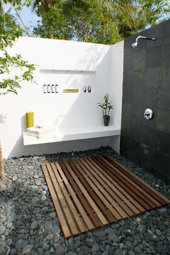 a contemporary outdoor shower of white concrete, tiles, pebbles on the floor and a wooden deck