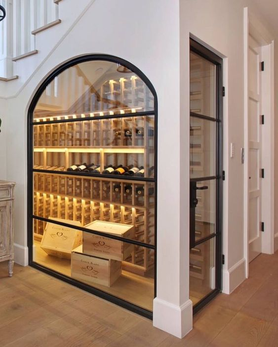 an under stairs wine cellar with an arched glass window and additional lights looks very cool