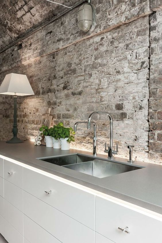 a contemporary industrial kitchen with rough grey brick walls and a ceiling plus stainless steel
