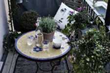 19 a monochromatic balcony with chairs and a lot of potted greenery is spruced up with a colorful mosaiic table