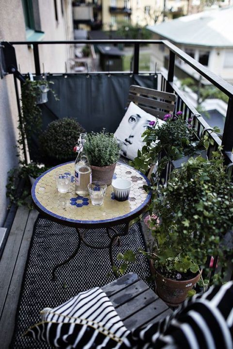 a monochromatic balcony with chairs and a lot of potted greenery is spruced up with a colorful mosaiic table