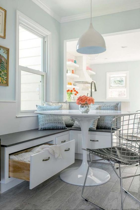a serene coastal breakfast space with a built-in banquette with drawers for storage