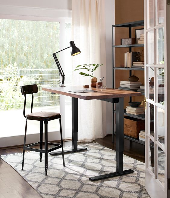 a stylish industrial desk of darkened metal and a wooden countertop plus a matching tall stool