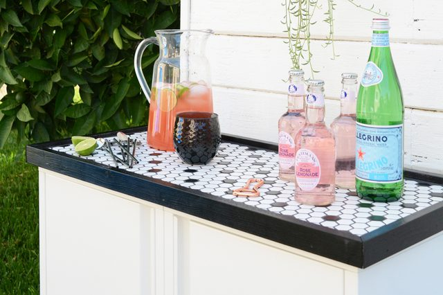 this chic outdoor bar with a mosaic on top is made using IKEA Josef cabinets and looks super chic
