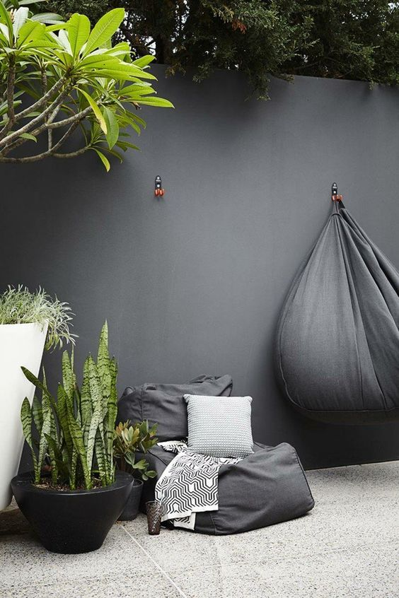 a black bean bag chair and potted plants for a minimalist outdoor space and some printed textiles