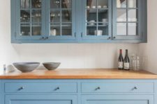 20 a gorgeous muted blue kitchen with butcher block countertops and matching wooden beams on the ceiling