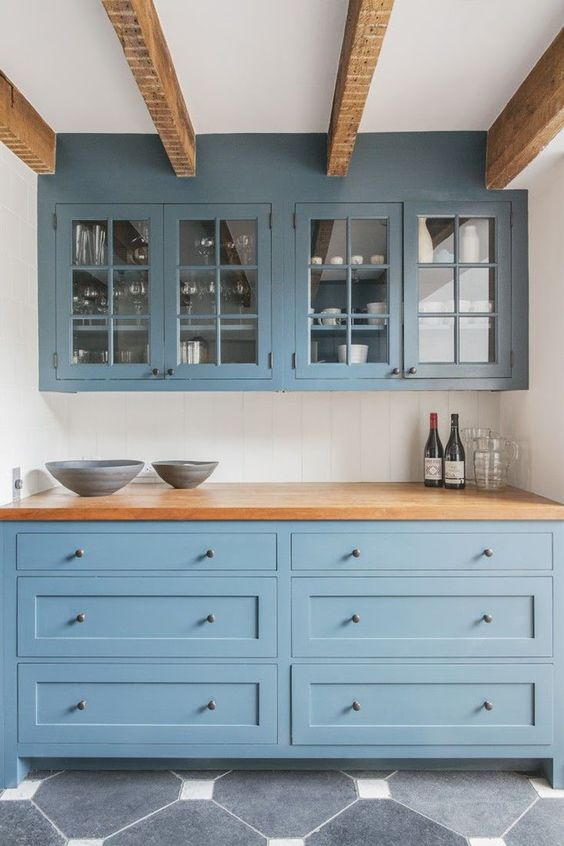 a gorgeous muted blue kitchen with butcher block countertops and matching wooden beams on the ceiling