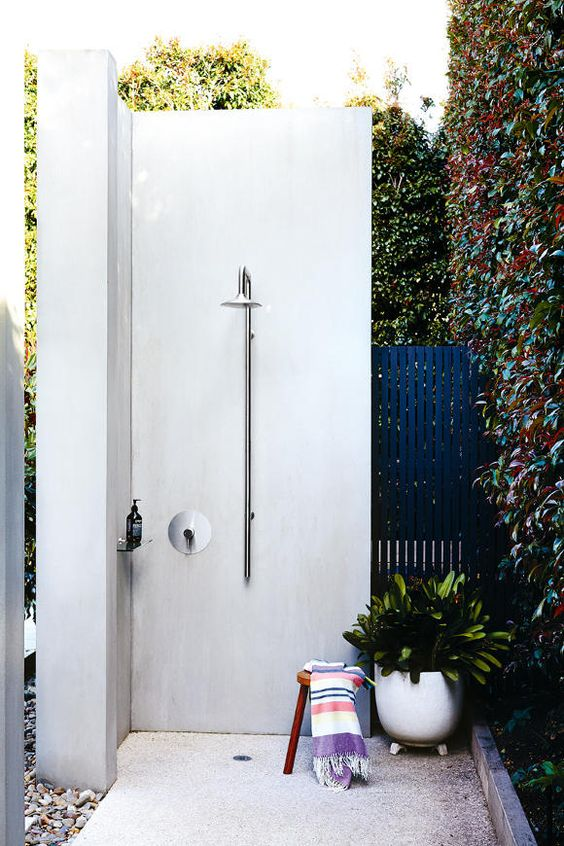 a modern white concrete shower with a small wooden stool and a potted plant for a lively feel