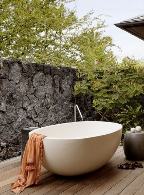 a peaceful space with a stone wall for privacy, a concrete table and an oval free-standing bathtub