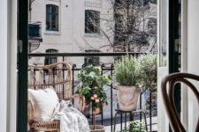 a small balcony with a wicker chair, potted greenery and baskets for storage