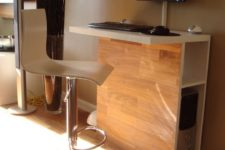 20 a tall and sleek stand desk work station with storage space inside and a large comfy stool