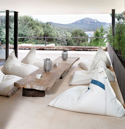 a relaxed casual outdoor dining space with several bean bag chairs and a low raw edge wooden table