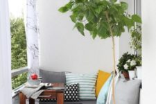 21 a small cozy balcony with an L-shaped upholstered bench, a small coffee table and potted plants